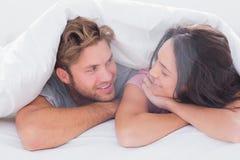 在被子微笑下的夫妇 免版税库存图片