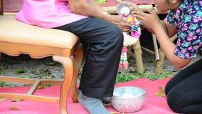 在被尊敬的长辈的手上的泰国人倾吐的水 股票视频