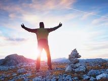 在被库存的石头的旅游指南在阿尔卑斯锐化 坚强的远足者享受在高山山的日落 免版税图库摄影