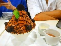 在被弄脏的人作为背景,特写镜头choco火山bingsu的Bingsu点心 图库摄影
