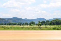 在被弄脏的山山脉和软的林木背景的木板条,在农田的空的木桌地板调遣粮食作物 图库摄影
