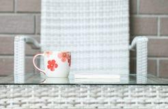 在被弄脏的木织法桌和椅子上的特写镜头逗人喜爱的杯子构造了背景 库存图片
