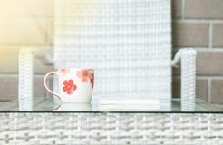 在被弄脏的木织法桌和椅子上的特写镜头逗人喜爱的杯子构造了背景 免版税图库摄影