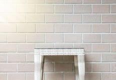 在被弄脏的棕色砖墙纹理背景的特写镜头木织法桌与太阳光,在房子的放松的美好的内部 图库摄影