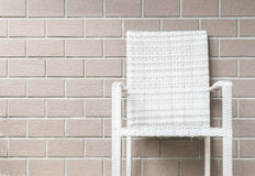 在被弄脏的棕色砖墙纹理背景,在房子概念的放松的美好的内部的特写镜头木织法椅子 免版税库存图片
