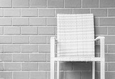 在被弄脏的棕色砖墙纹理背景,在房子概念的放松的美好的内部的特写镜头木织法椅子 库存图片