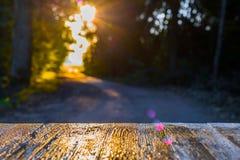 在被弄脏的森林公路背景的空的土气木台式  库存图片