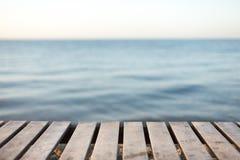 在被弄脏的海背景前面的木桌 库存照片