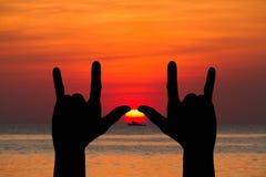 在被弄脏的自然金黄日落的手势我爱你标志剪影在海滩 库存照片