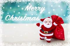在被弄脏的蓝色背景的圣诞快乐与圣诞老人和红色礼物袋子 库存图片