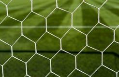 在被弄脏的足球场背景的足球网 免版税库存图片