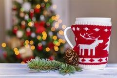 在被弄脏的轻的背景的被编织的圣诞节杯 免版税库存照片