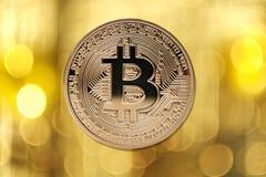 在被弄脏的轻的背景的金黄bitcoin 免版税库存照片