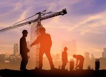 在被弄脏的c的一个建筑工地现出轮廓建筑工人 图库摄影
