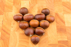 在被形成的一块木板材的秋天季节性果子西班牙栗子 库存图片