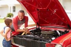 在被恢复的经典汽车的祖父和孙女工作 免版税图库摄影