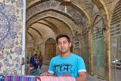 在被成拱形的走廊背景的伊朗sallesman画象在b的 免版税库存照片