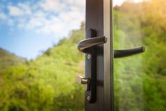 在被打开的黑现代玻璃门的门把手有绿色自然和blus天空背景 软绵绵地集中 库存图片