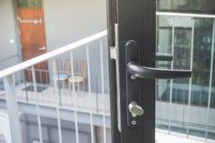 在被打开的黑现代玻璃门的门把手那出去对阳台 软绵绵地集中 免版税库存照片
