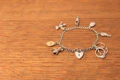 在被抓的木背景的银色魅力镯子 免版税库存图片