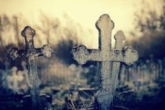 在被投掷的坟墓的老偏重坟墓十字架在公墓 免版税图库摄影