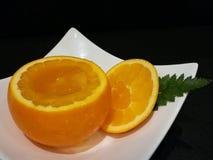 在被挖空的桔子的橙色果冻点心和切片橙色在白色板材隔绝黑背景,时髦的点心食物,新鲜的a 免版税库存照片