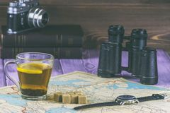 在被摆一本旧书的桌子上,地图 杯糖和双筒望远镜茶和片断  并且有影片照相机 库存照片