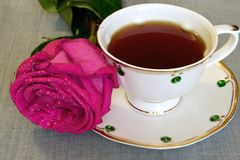 在被摆玫瑰的桌子上,站立在瓷杯旁边用茶 库存图片