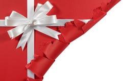 在被撕毁的开放红色纸背景的圣诞节或生日白色缎礼物丝带弓 免版税库存图片