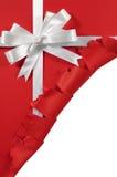在被撕毁的开放红色纸背景的圣诞节或生日白色缎礼物丝带弓 免版税库存照片