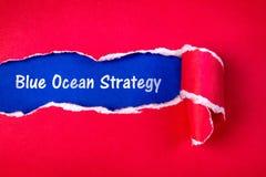 在被撕毁的红色纸的蓝色海洋战略与蓝色的词和空间 免版税库存图片