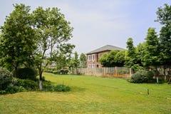 在被操刀的房子前的被灌溉的草坪在晴朗的夏天 库存图片