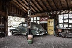 在被放弃的技工车库的生锈的老葡萄酒汽车 免版税库存照片