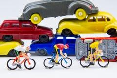 在被放弃的汽车铈的微型微小的玩具骑自行车者乘驾自行车 库存图片