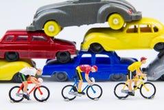 在被放弃的汽车铈的微型微小的玩具骑自行车者乘驾自行车 图库摄影
