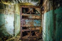 在被放弃的苏联军事地堡的老生锈的钢装甲的门 库存照片