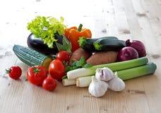 在被日光照射了厨房用桌的蔬菜 图库摄影