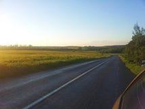 在被日光照射了象草的草甸旁边的美丽的空的路 免版税库存图片