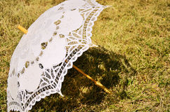 在被染黄的草的有花边的遮阳伞 库存图片