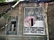 在被毁坏的墙壁上的老海报俄语 图库摄影
