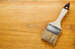 在被涂清漆的木板的画笔有文本的地方的 免版税库存照片