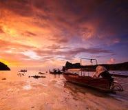 在被淹没的岩石中的渴望尾巴小船在日落 库存照片