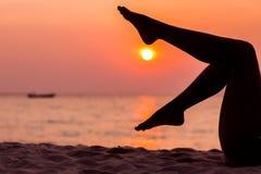 在被点燃的海背景的女性腿剪影 免版税库存图片