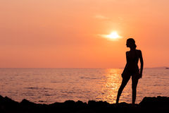 在被点燃的海背景的常设妇女剪影 免版税图库摄影