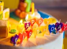 在被点燃的蜡烛写的生日快乐在五颜六色的背景 库存照片