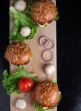 在被烘烤的小圆面包、水多的酥脆蘑菇汉堡小圆面包、健康膳食午餐的和晚餐的芝麻 免版税库存照片
