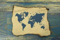 在被烧的纸的世界地图在蓝色老木背景 库存照片