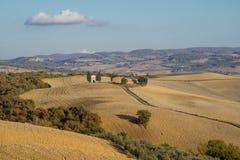在被犁的领域中间的教堂在与一朵云彩的秋天托斯卡纳在天空 免版税库存照片