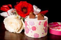 在被环绕的礼物盒的心形的巧克力爱与玫瑰情人节 图库摄影