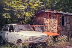 在被破坏的拖车旁边的被放弃的汽车 免版税库存图片